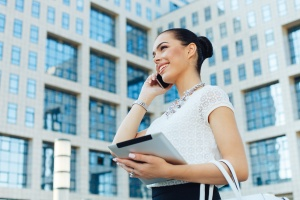 Young businesswoman outside on phone with digital tablet in hand