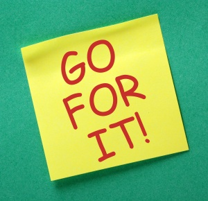 The phrase Go For It in red text on a yellow sticky note posted on a green notice board